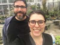 A man and a woman smiling at the camera while standing in a greenhouse